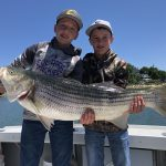 Two kids with a big striped bass