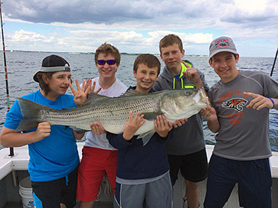 Group of kids showing their big striped bass they caught in Boston, MA